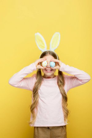 Photo for Cheerful child with bunny ears covering eyes with easter eggs isolated on yellow - Royalty Free Image
