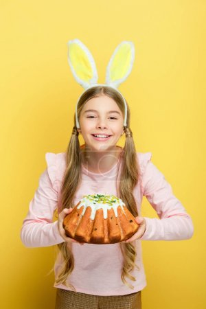 Photo for Smiling kid with bunny ears holding easter cake isolated on yellow - Royalty Free Image