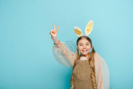 Photo pour Enfant heureux avec des oreilles de lapin montrant signe de paix isolé sur bleu - image libre de droit