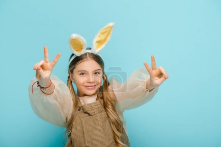 Photo for Cheerful kid with bunny ears showing peace sign isolated on blue - Royalty Free Image