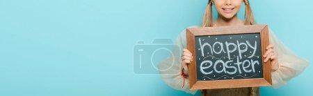 Panoramaaufnahme eines fröhlichen Kindes mit Kreidetafel und fröhlichem Osteraufdruck isoliert auf blau