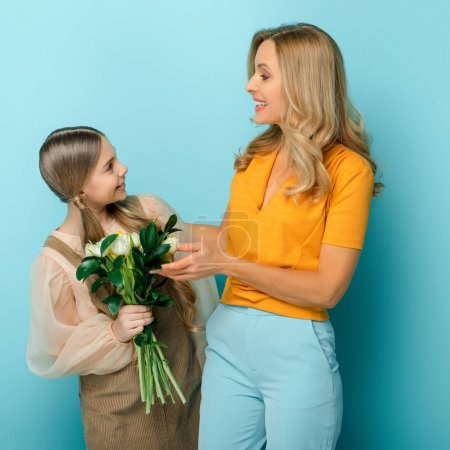 Photo for Cheerful mother looking at daughter with tulips isolated on blue - Royalty Free Image