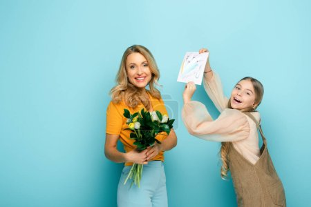 Photo for Happy daughter holding greeting card with 8 march lettering near mother with tulips on blue - Royalty Free Image