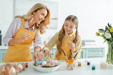 Photo pour Mère heureuse regardant sa fille prendre des œufs de Pâques peints - image libre de droit