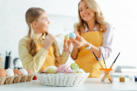 Photo for Selective focus of basket with painted easter eggs near happy mother and daughter - Royalty Free Image