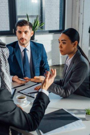 Photo pour Des partenaires d'affaires multiculturels discutent avec un traducteur dans un bureau moderne - image libre de droit