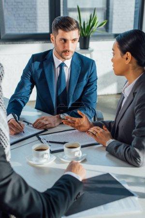 Photo pour Des partenaires d'affaires multiculturels discutent du contrat d'une rencontre avec un traducteur de bureau avec des tasses de café - image libre de droit