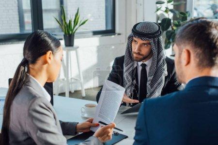 Photo pour Des partenaires d'affaires multiculturels discutent de contrat pour une rencontre avec un traducteur professionnel en poste - image libre de droit