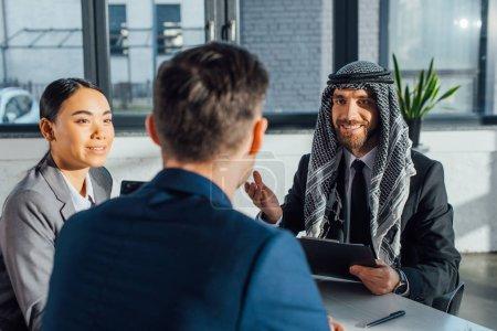 Photo pour Heureux partenaires d'affaires multiculturels discuter contrat sur la réunion avec traducteur au bureau - image libre de droit