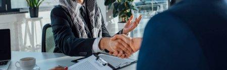 Foto de Plano panorámico de empresarios multiétnicos estrechando la mano y teniendo trato en la reunión - Imagen libre de derechos
