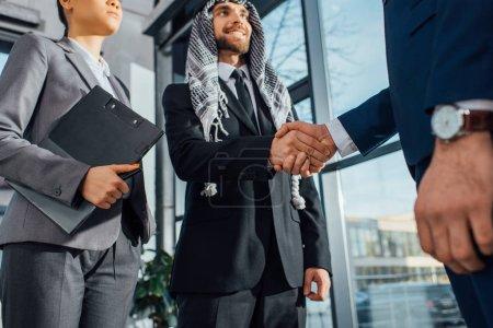 Photo pour Homme d'affaires arabe joyeux serrant la main d'un partenaire lors d'une réunion avec un traducteur au bureau - image libre de droit