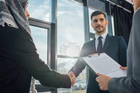 Photo pour Homme d'affaires arabe professionnel serrant la main d'un partenaire lors d'une réunion avec un traducteur au bureau - image libre de droit