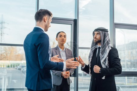 Photo for Multicultural businesspeople discussing work on meeting with translator in modern office - Royalty Free Image