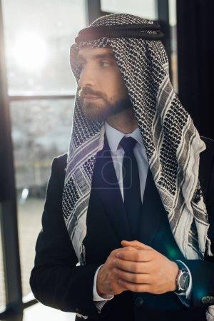 Photo pour Bel homme d'affaires arabe debout dans le bureau avec rétroéclairage - image libre de droit