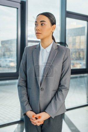 Photo pour Asiatique femme d'affaires en costume gris debout dans bureau moderne - image libre de droit