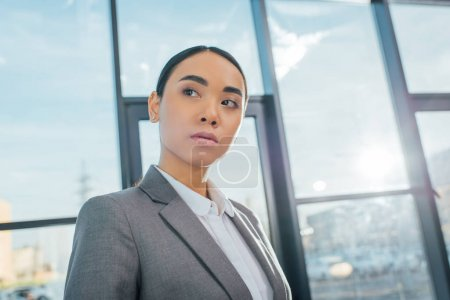 executive asian businesswoman in grey suit standing in modern office