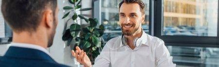 Photo pour Photo panoramique d'un traducteur souriant travaillant avec un homme d'affaires dans un bureau moderne - image libre de droit