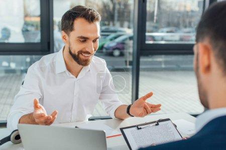 Photo pour Un traducteur souriant travaillant avec un homme d'affaires et des documents dans un bureau moderne - image libre de droit