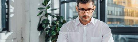 Photo pour Plan panoramique de traducteur professionnel masculin dans les lunettes de travail dans le bureau moderne - image libre de droit