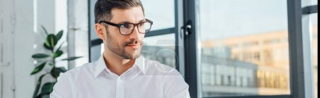 Photo for Panoramic shot of professional male translator in eyeglasses sitting in modern office - Royalty Free Image