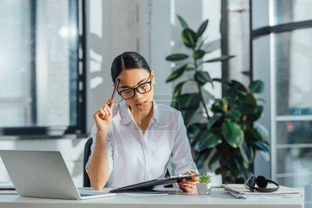 Photo pour Un traducteur asiatique travaillant avec un ordinateur portable et des documents dans un bureau moderne - image libre de droit