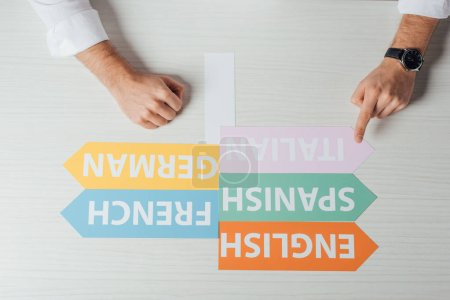 Photo for Top view of translator pointing at arrows with languages - Royalty Free Image
