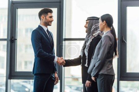 Photo pour Des partenaires d'affaires professionnels multiculturels serrent la main d'un traducteur en poste - image libre de droit
