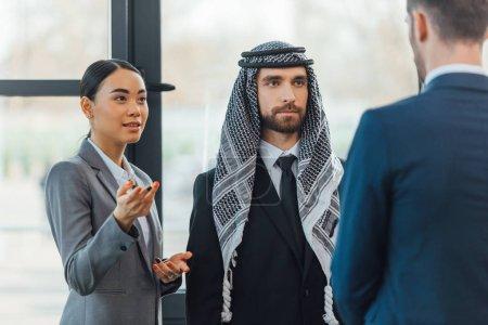 Photo pour Des partenaires d'affaires multiethniques lors d'une rencontre avec un traducteur en poste - image libre de droit