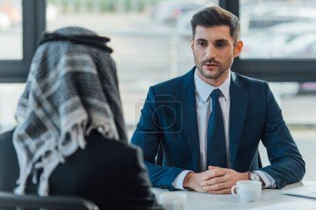 Photo pour Entretien d'un homme d'affaires arabe avec un partenaire dans un bureau moderne - image libre de droit