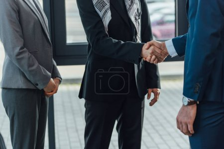 cropped view professional businessmen shaking hands and having deal in modern office