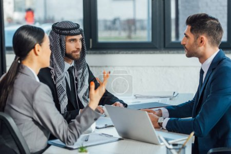 multicultural business partners with laptop and documents on meeting with translator in office