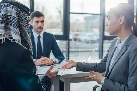 Photo pour Des partenaires commerciaux multiculturels discutant de leur rencontre avec un traducteur en poste - image libre de droit