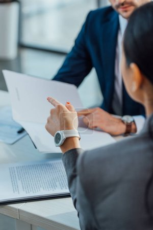 Photo pour Vue en rafale d'un homme et d'une femme d'affaires discutant de contrat dans un bureau moderne - image libre de droit