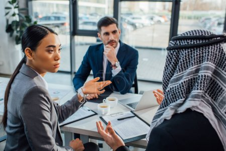 multicultural businesspeople discussing contract on meeting with translator in office
