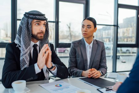 Photo for Arabic business partners discussing contract on meeting with translator in office - Royalty Free Image