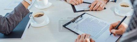 Photo pour Photo panoramique de gens d'affaires ayant un contrat et des tasses à café en réunion au bureau - image libre de droit