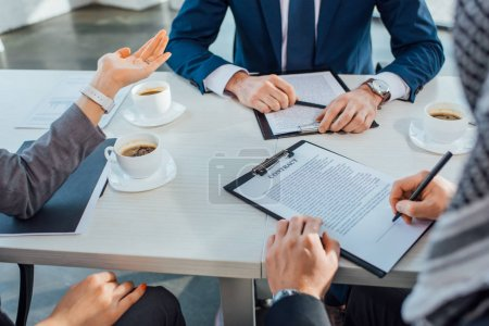 Photo for Cropped view of professional business partners signing contract on meeting in office with coffee cups - Royalty Free Image