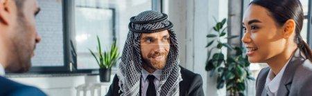 Photo pour Photo panoramique de partenaires d'affaires multiethniques heureux lors d'une rencontre avec un traducteur en poste - image libre de droit