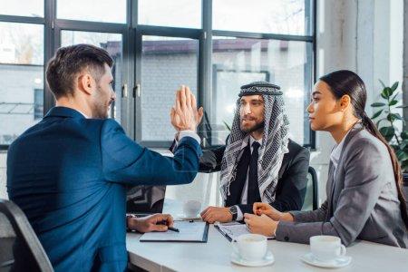 Photo pour Partenaires commerciaux multiculturels positifs donnant cinq sur la réunion avec le traducteur au bureau - image libre de droit