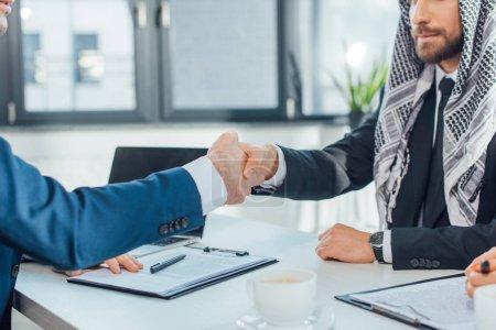 Photo pour Vue recadrée d'hommes d'affaires multiethniques serrant la main et ayant affaire à la réunion - image libre de droit