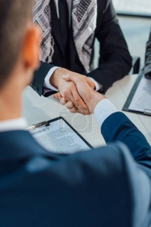 Photo for Cropped view of multiethnic businessmen shaking hands on meeting - Royalty Free Image