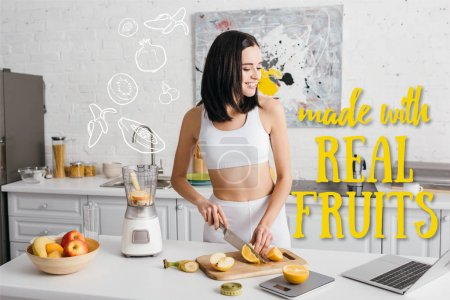 Smiling fit sportswoman looking at laptop while cutting fruits near blender on kitchen table, made with real fruits illustration