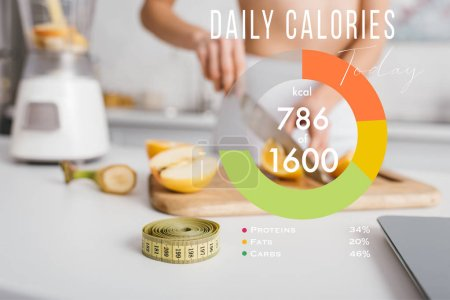 Photo for Selective focus of measuring tape and scales near fit girl cutting fresh fruits for smoothie on kitchen table, daily calories illustration - Royalty Free Image