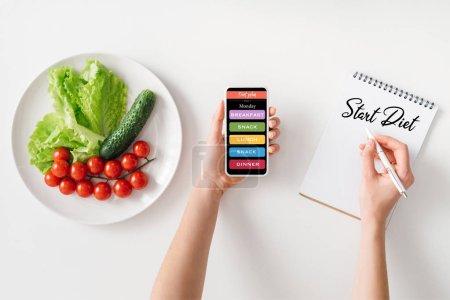 Photo pour Vue du dessus de la femme tenant smartphone et l'écriture dans un carnet avec commencer le régime alimentaire lettrage près des légumes mûrs sur plaque sur fond blanc - image libre de droit