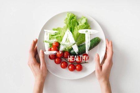 Photo pour Vue du haut d'une femme tenant une assiette de légumes crus sur fond blanc - image libre de droit
