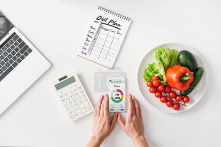 Photo pour Vue du dessus de la femme tenant smartphone près de la calculatrice, ordinateur portable et légumes sur fond blanc - image libre de droit