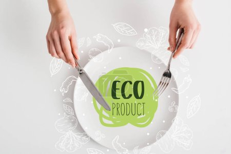 Top view of woman holding cutlery on plate with eco product illustration on white background