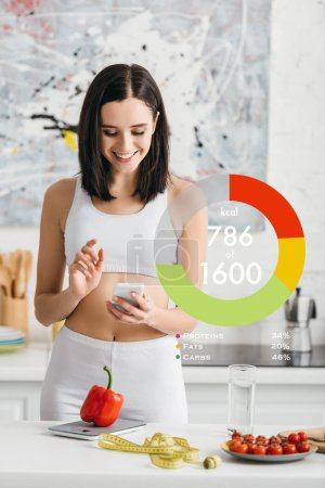 Smiling sportswoman using smartphone near measuring tape, vegetables and scales on kitchen table, calorie counting illustration