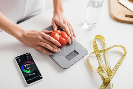Photo for Cropped view of woman putting tomato on scales near smartphone with calorie counting app and measuring tape on kitchen table - Royalty Free Image