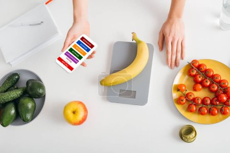 Top view of girl holding smartphone with diet plan while weighing banana on kitchen table with vegetables